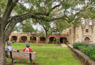 pausing at a mission during a Texas bike tour