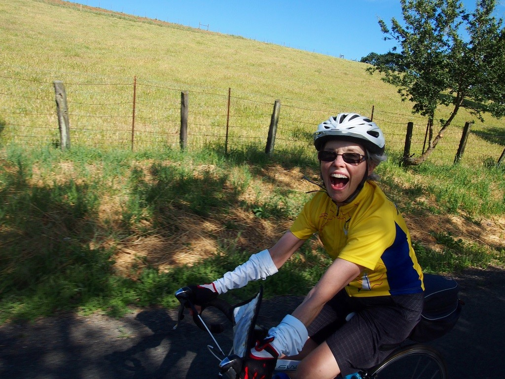 An elated cyclist pedals her Cannondale through California Sonoma wine country feeling happiness