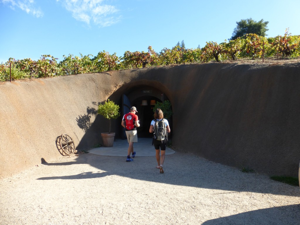 Sojourn guests enter the wine cave at Bella during a California Wine Country Bike Tour